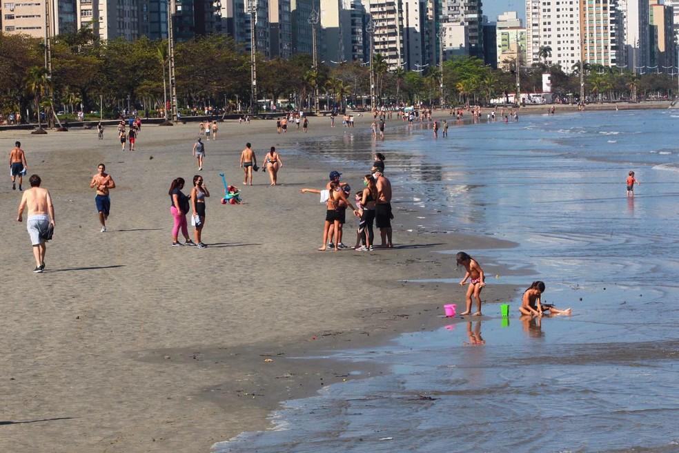 Crianças brincando na faixa de areias e pequenos grupos reunidos em praia de Santos (SP) — Foto: Matheus Tagé/ A Tribuna Jornal