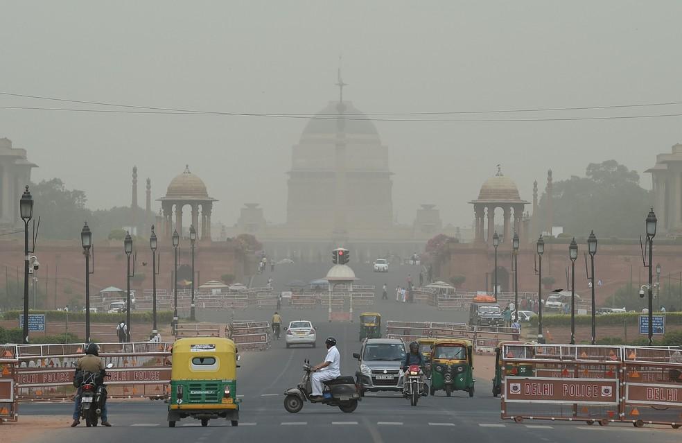 Veículos são vistos em meio à poeira na paisagem de Nova Deli, na Índia — Foto: Prakash Singh/AFP