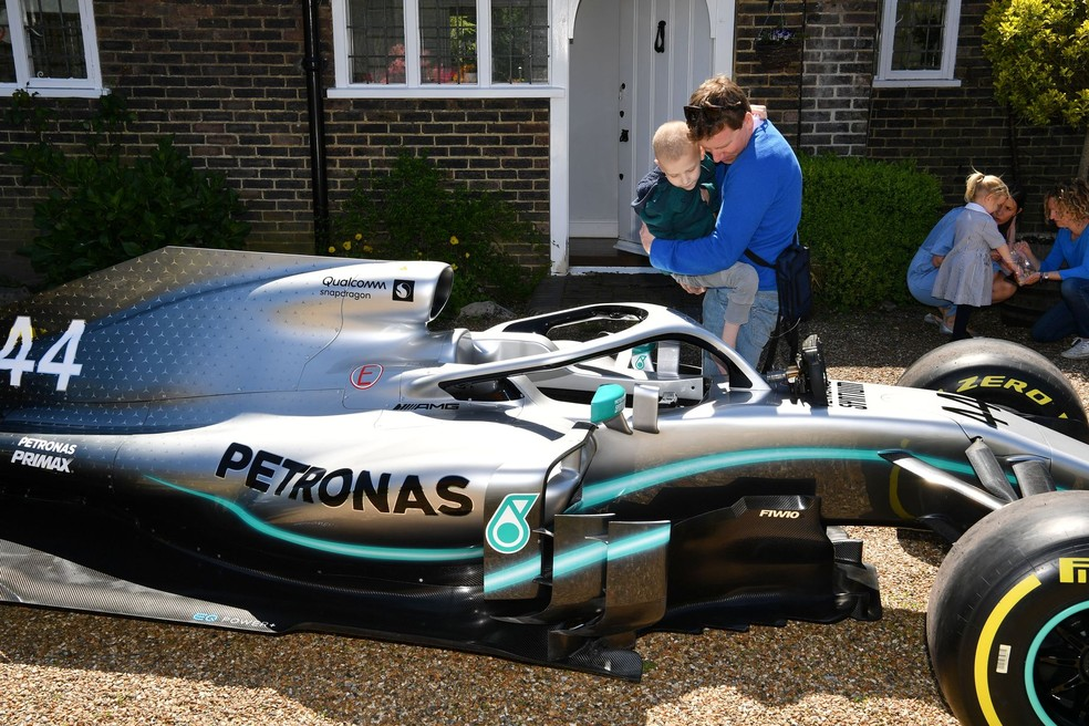 Harry com o pai James Shaw e o carro de Lewis Hamilton — Foto: Surrey Live