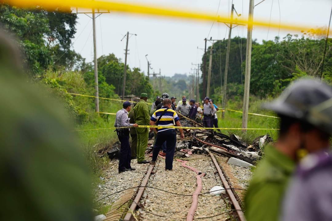 Equipe de resgate e busca trabalha entre destroços de avião que pararam sobre trilhos de uma rodovia após acidente aéreo em Havana