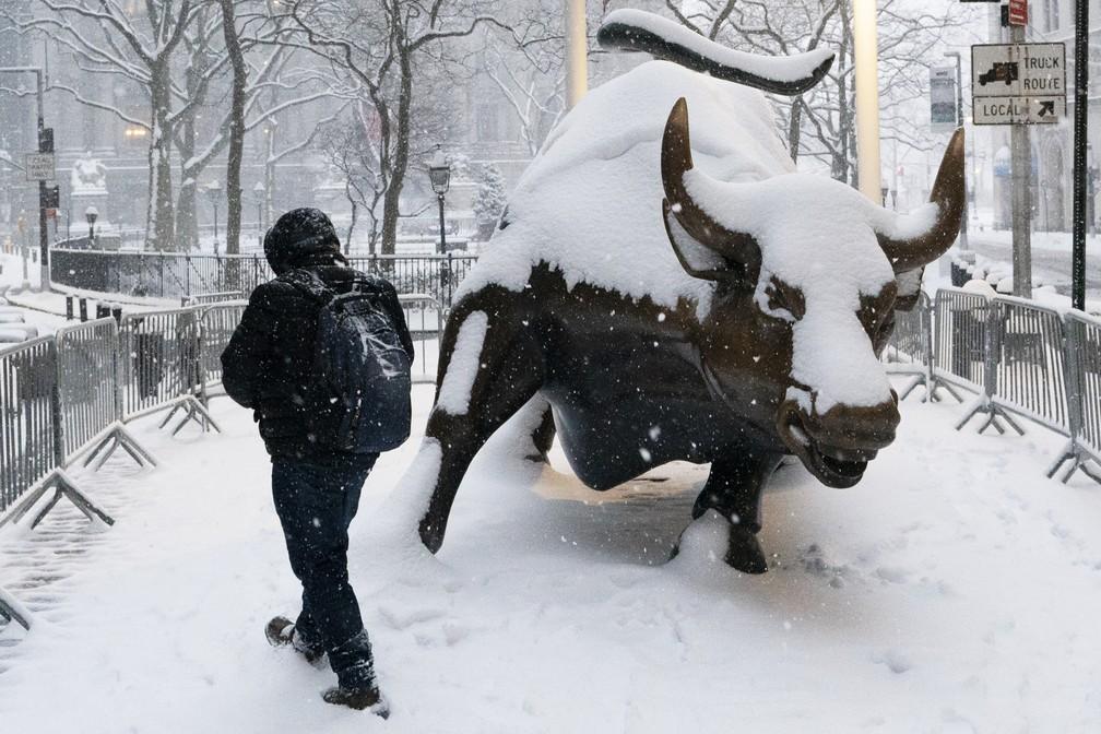 Homem passa pela estátua do touro em Wall Street durante nevasca em Nova York em 1º de fevereiro de 2021 — Foto: Mark Lennihan/AP
