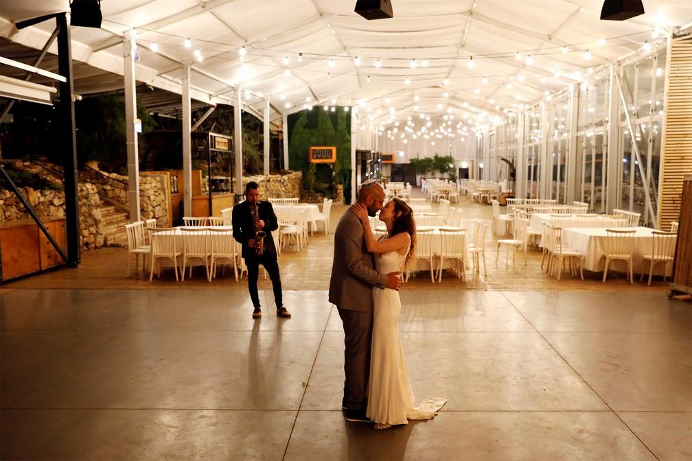 18 de março - Recém-casados, Roni Ben-Ari e Yonatan Meushar dançam sozinhos em festa sem convidados, numa casa de eventos que passou a oferecer pequenas cerimônias de graça para noivos que tiveram as festas canceladas devido ao coronavírus, em Ein Hemed, Israel — Foto: Ronen Zvulun/Reuters