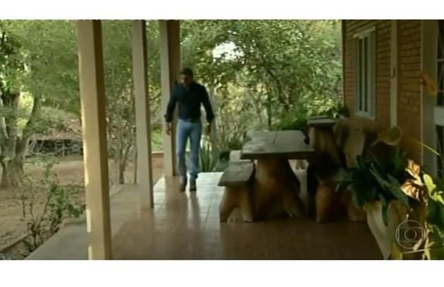 Caio na varanda de sua casa, que tem móveis rústicos de madeira maciça (Foto: Reprodução)