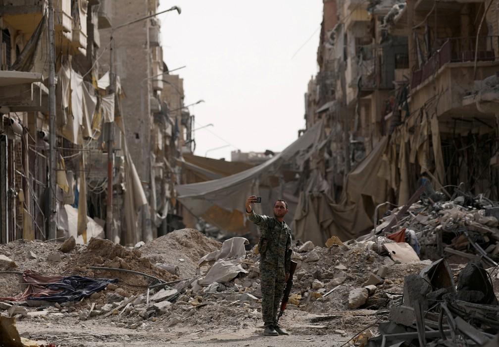 Um combatente das Forças Democráticas da Síria tira uma selfie perto de entulhos de um local destruído, em Raqqa, na Síria (Foto: Rodi Said/Reuters)