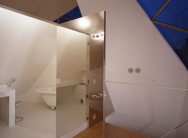 Dentro do banheiro, a porta é coberta por espelho, o que faz o cômodo parecer maior (Foto: Makoto Yoshida/ Atelier Tekuto/ Reprodução)