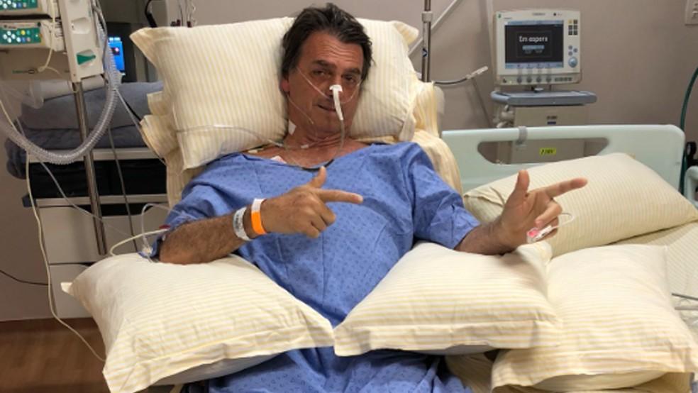 Foto postada por filho de Jair Bolsonaro mostra candidato em poltrona do Hospital Albert Einstein, em São Paulo, fazendo sinais de armas — Foto: Reprodução / Twitter / Flavio Bolsonaro