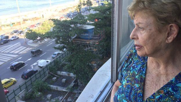 A moradora Alice Gonzaga, vizinha à obra, manda cartas com frequência a autoridades e jornais cariocas se queixando de 'descaso' e pedindo que calçada ocupada por tapumes seja liberada. (Foto: Júlia Dias Carneiro/BBC News Brasil)