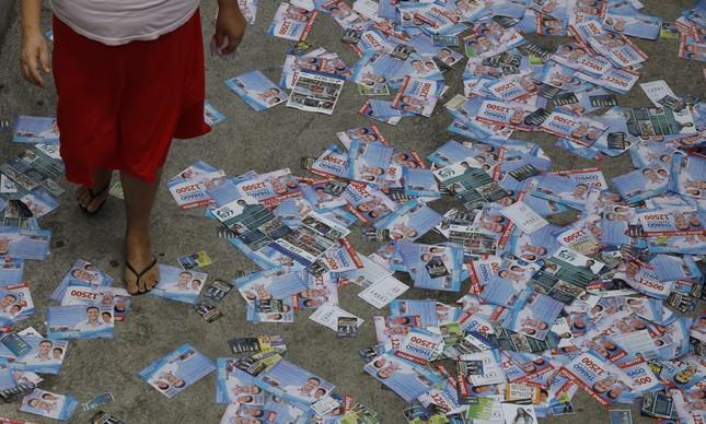Eleitora caminha sobre panfletos na Rocinha