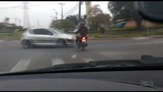 Suspeitos furam sinal vermelho e batem moto contra carro durante perseguição policial; VÍDEO