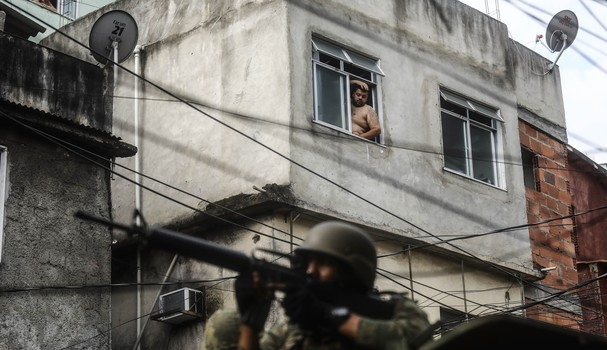 RIO DE JANEIRO, BRAZIL - SEPTEMBER 24:  A man watches from a window as a Brazilian soldier aims his weapon while on patrol in the Rocinha 'favela' community on September 24, 2017 in Rio de Janeiro, Brazil. The Brazilian Army and other armed forces entered (Foto: Getty Images)
