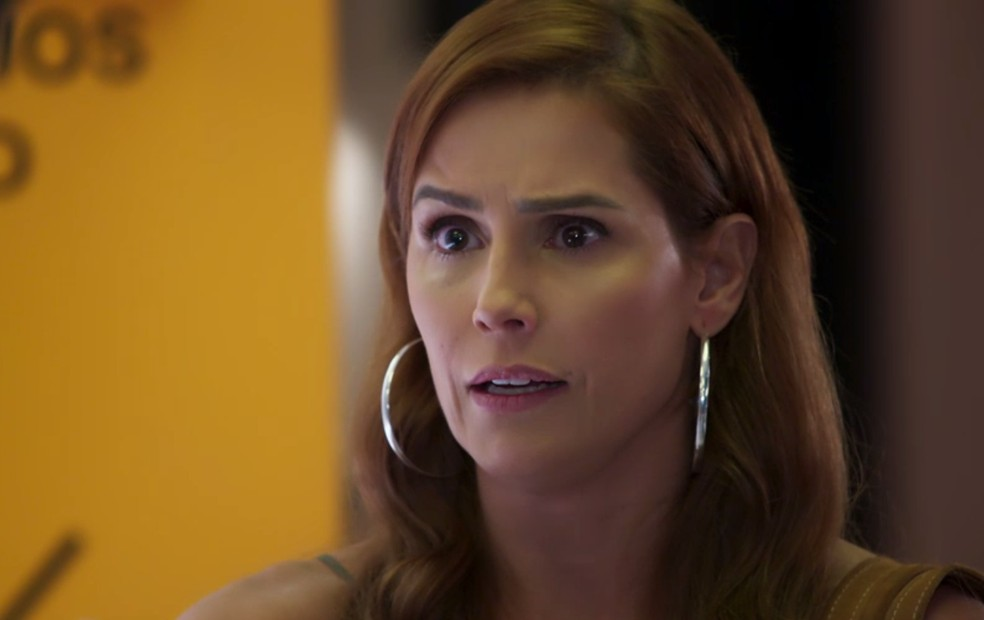 Alexia (Deborah Secco) vê entrevista de sua irmã na TV — Foto: Globo