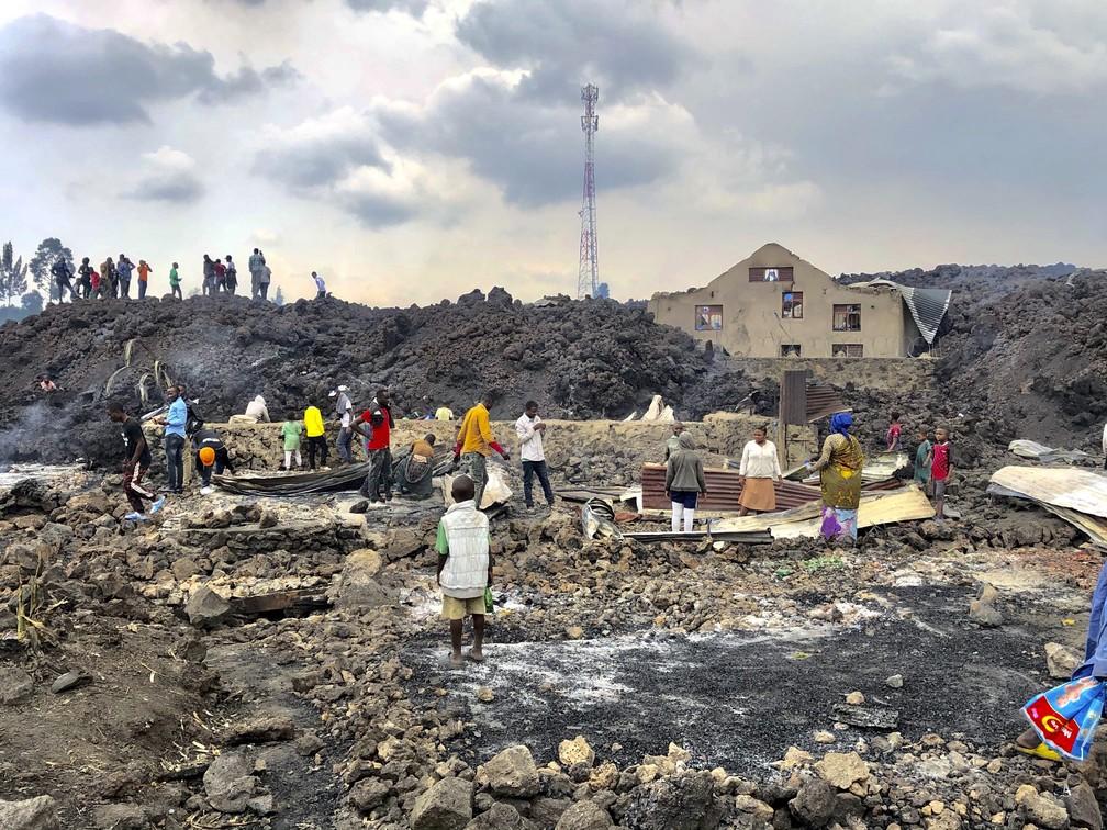 Pessoas em meio a lava fria após a erupção noturna do vulcão no monte Nyiragongo em Goma, na República Democrática do Congo, no domingo (23) — Foto: Clarice Butsapu/AP