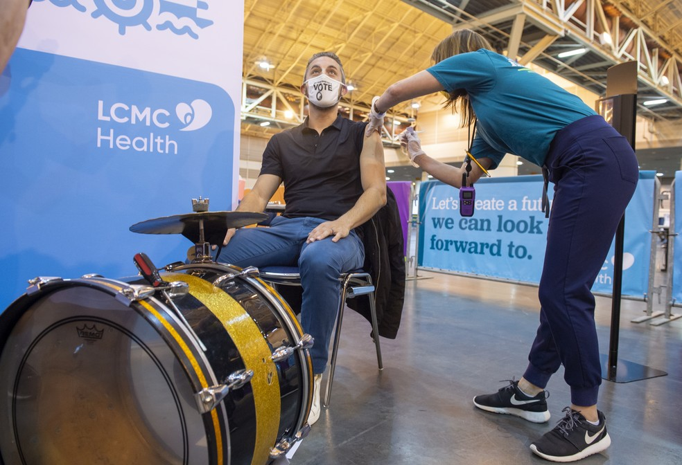O bateirista Kyle Sharamitaro recebe dose da vacina da Johnson & Johnson contra a Covid-19 em um centro de convenções em New Orleans nesta quinta-feira (4). Sharamitaro depois se juntou à Soul Brass Band, que estava tocando na entrada do local. — Foto: Chris Granger/The Advocate via AP
