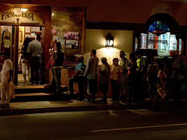 Moradores de El Hatillo, nas proximidades de Caracas, fizeram fila no último sábado (23) em uma padaria para comprar pão em dia de corte de energia (Foto: Foto AP/Fernando Llano)