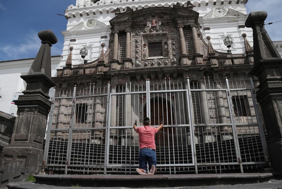 Homem reza em frente à igreja de São Francisco, na sexta-feira (10), em Quito, no Equador  — Foto: Dolores Ochoa/ AP