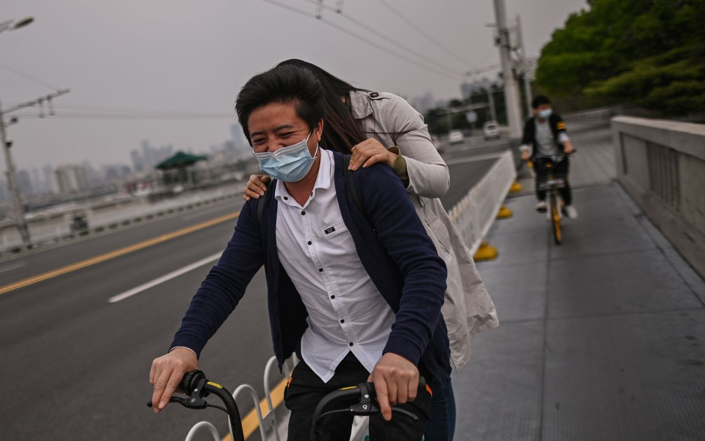 Pessoas com máscaras atravessam de bicicleta a Ponte Wuhan, em Wuhan, após o fim da quarentena na província de Hubei, na China, na quarta-feira (8) — Foto: Hector Retamal/AFP