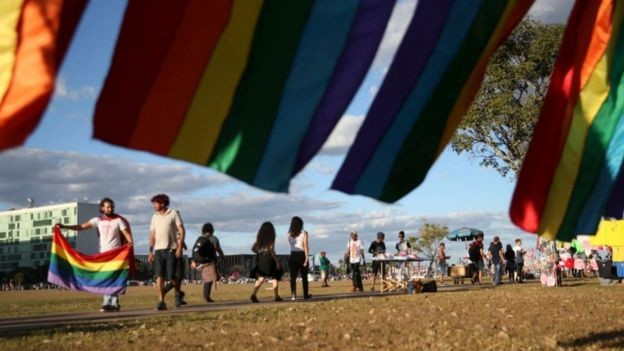 A bandeira LGBT atual tem seis cores - e não oito como a de Cusco. Na foto, manifestantes com a flâmula na Parada LGBT de Brasília de 2018 (Foto: JOSÉ CRUZ / AGÊNCIA BRASIL)
