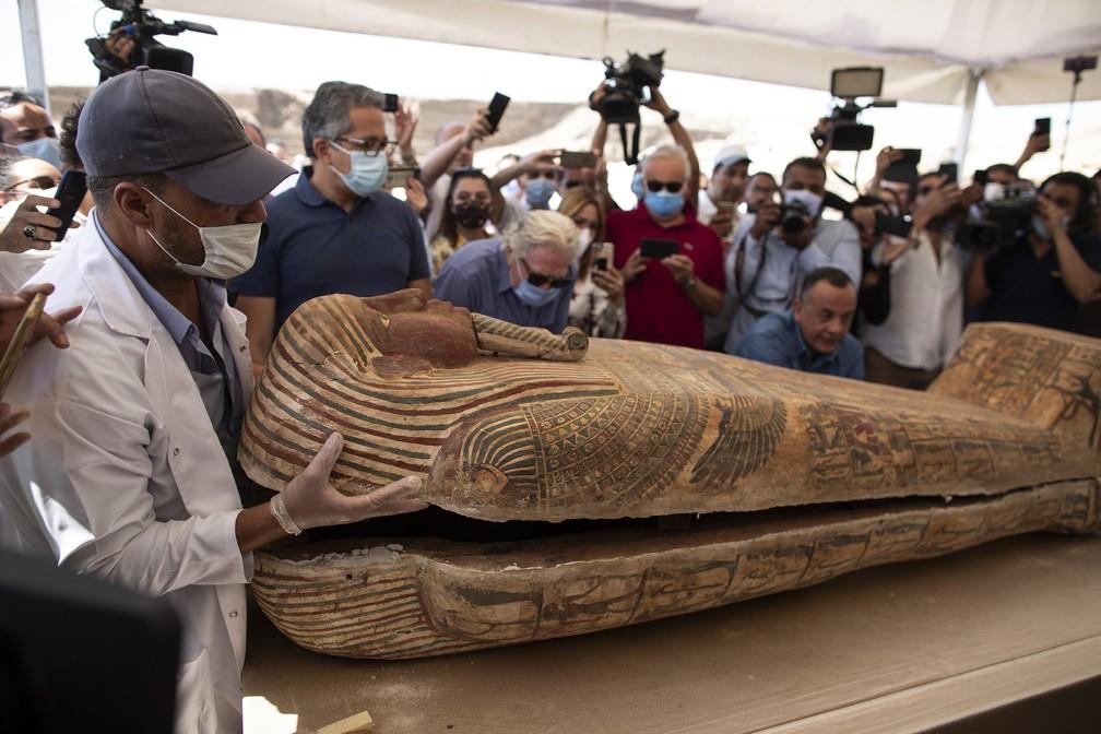 Sarcófago é aberto no sítio arqueológico de Saqqara, 30 quilômetros ao sul do Cairo, Egito, neste sábado (3), na presença de jornalistas e funcionários. O Ministério de Antiguidades e Turismo do Egito afirma que pelo menos 59 sarcófagos com múmias dentro foram encontrados — Foto: Mahmoud Khaled/AP
