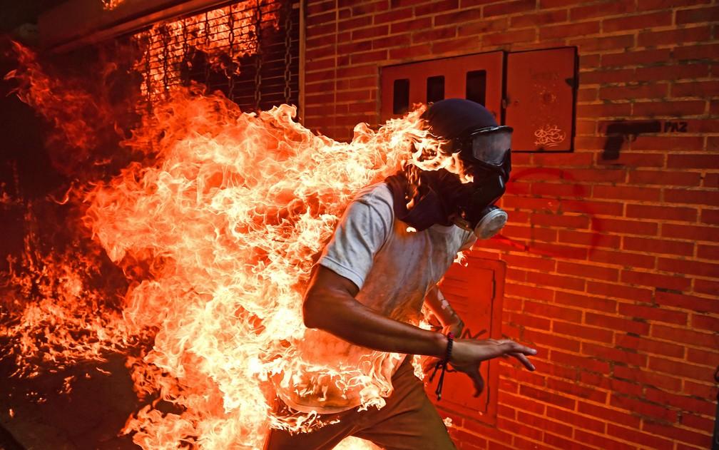 O estudante Víctor Salazar corre, em chamas, após a explosão do tanque de gasolina de uma moto durante protesto em Caracas, na Venezuela, no dia 3 de maio de 2017 (Foto: Ronaldo Schemidt/AFP)