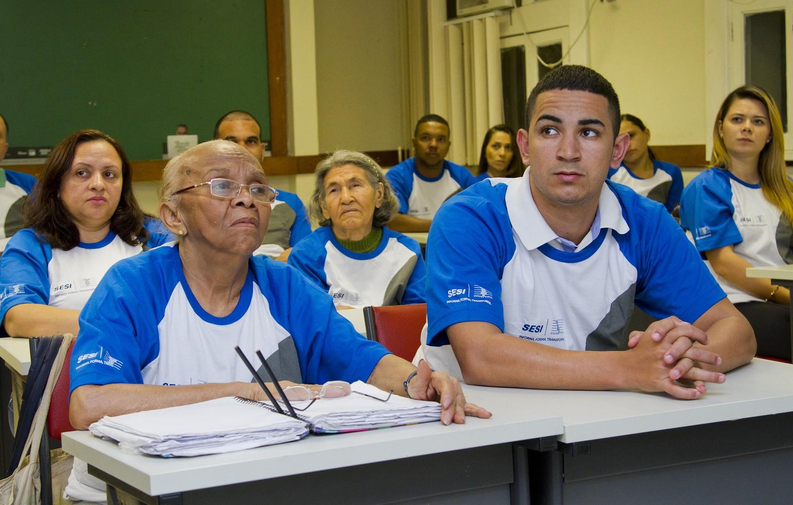 Turma de EJA em sala de aula, com estudantes jovens, adultos e idosos sentados, vestindo camisetas brancas com golas e mangas azuis, do SESI.