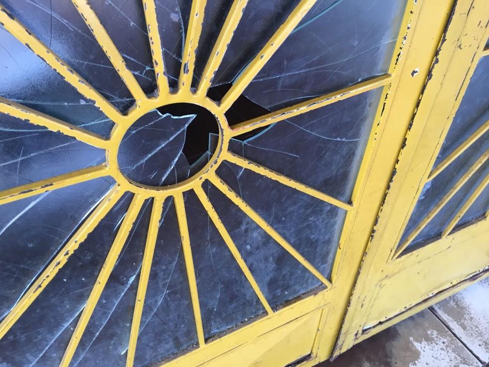 Porta do mercado ficou danificado com disparo feito por um dos ladrões — Foto: Márcio Falcão/TVCA