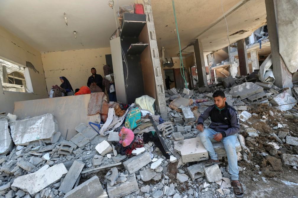 Um menino palestino se senta sobre os escombros de casas destruídas após os ataques aéreos e de artilharia israelenses na sexta-feira (14), no norte da Faixa de Gaza, na sexta-feira (14)   — Foto: Mohammed Salem/Reuters