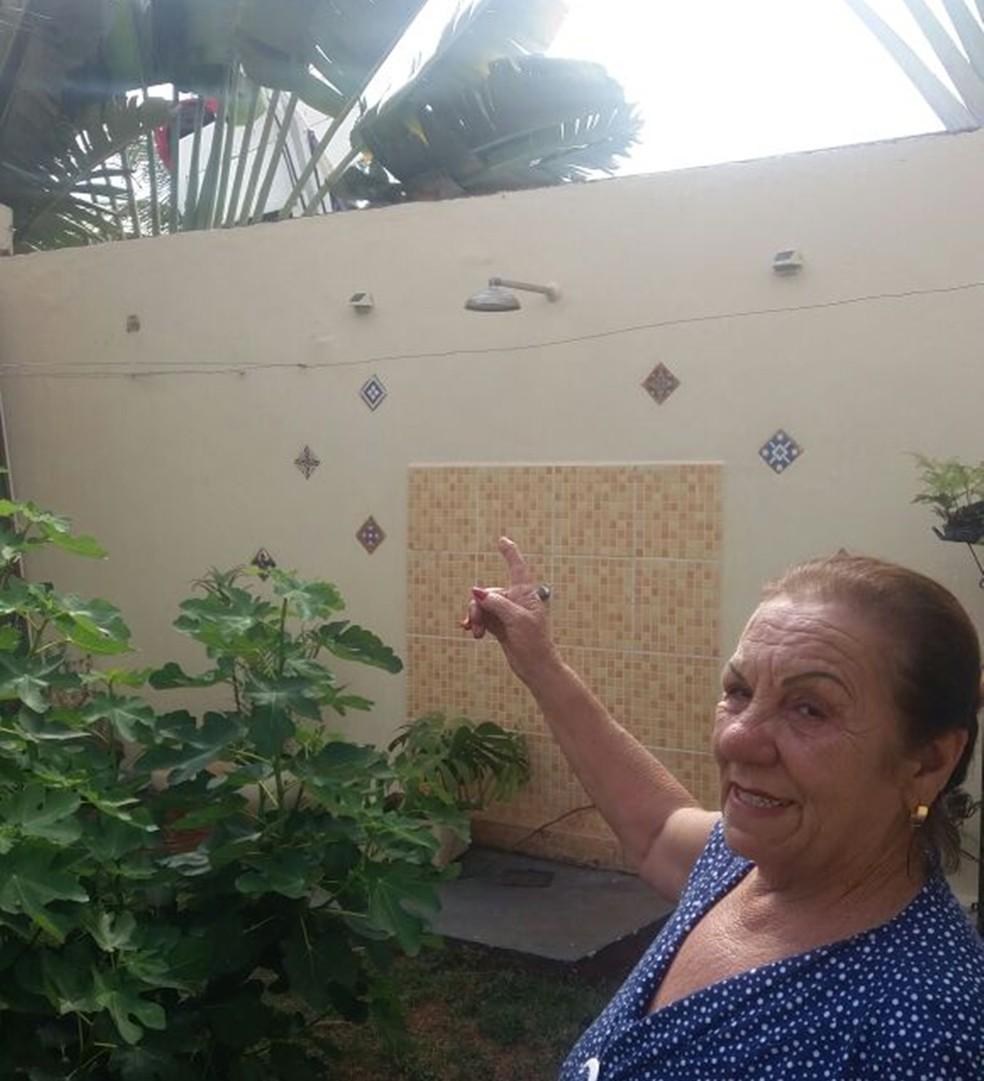 Aurora mostra a cauda do avião que caiu, atrás das árvores (Foto: Bruna Alves/G1)