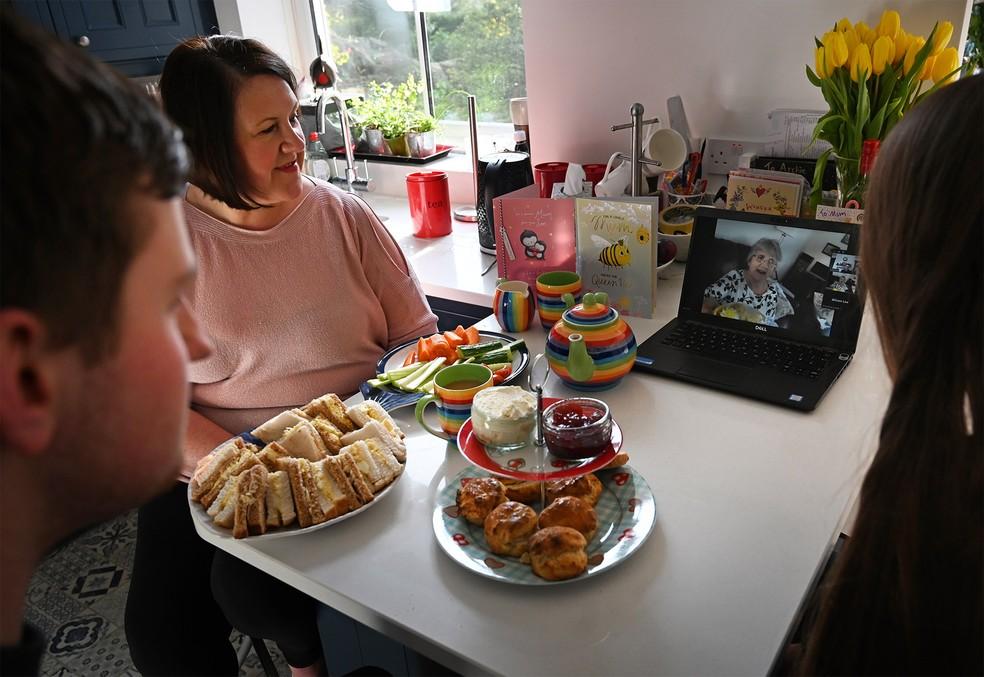 Família na Inglaterra faz conversa de vídeo em grupo para falar simultaneamente com a mãe e a avó pela internet durante o Dia das Mães britânico — Foto: Paul Ellis/AFP