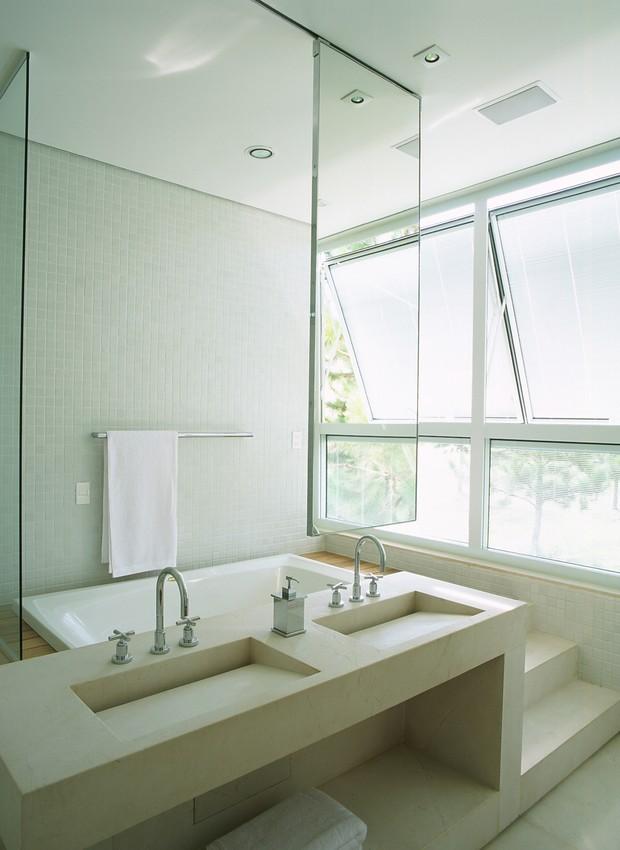 A banheira fica atrás da bancada, criando um ambiente discreto e clean. Projeto assinado pelo arquiteto Arthur Casas.  (Foto: Tuca Reinés / Casa e Jardim)