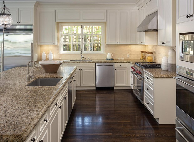 A cozinha possui armários claros e clássicos (Foto: Berkshire Hathaway HomeServices/ Reprodução)