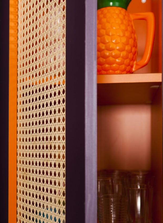 Armário da cozinha com portas feitas de palhinha. Imagem produzida para a matéria sobre o conceito do apartamento decorado pela arquiteta e moradora Andrea Murao, misturando cores e texturas, em Ubatuba, litoral norte de São Paulo (Foto: Edu Castello / Casa e Jardim)