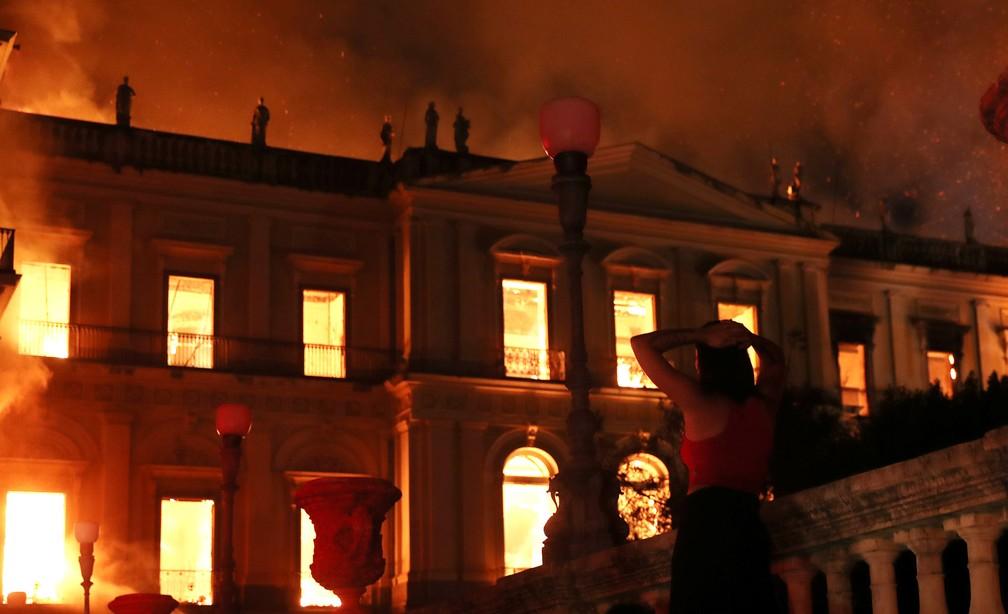 Uma mulher reage ao ver o incêndio no prédio do Museu Nacional, no Rio de Janeiro, na noite de domingo (2) (Foto: Ricardo Moraes / Reuters)