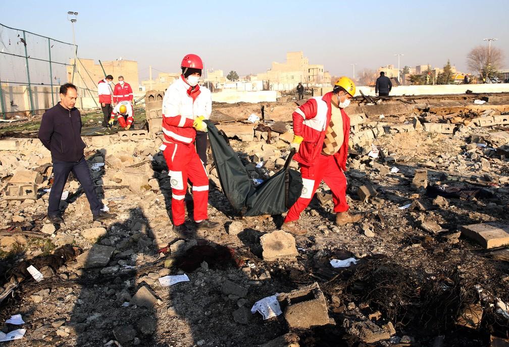Equipes de resgate retiram corpo dos destroços do avião ucraniano que caiu com 176 pessoas perto do aeroporto de Teerã, no Irã, nesta quarta-feira (8) — Foto: AFP