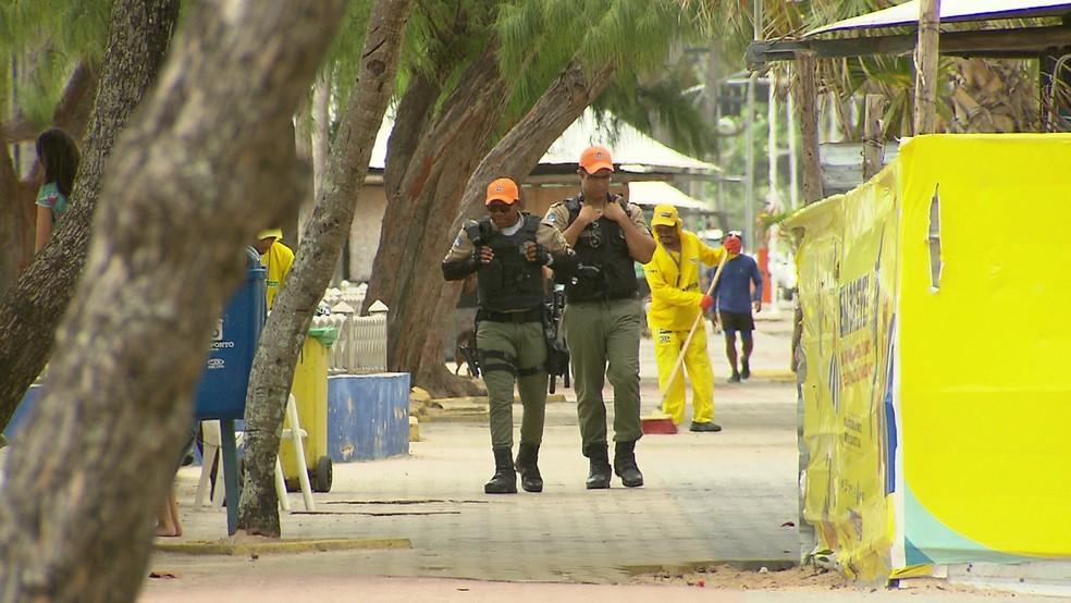 Policiais militares caminham pela orla da Praia de Boa Viagem, no Recife (Foto: Reprodução/TV Globo)