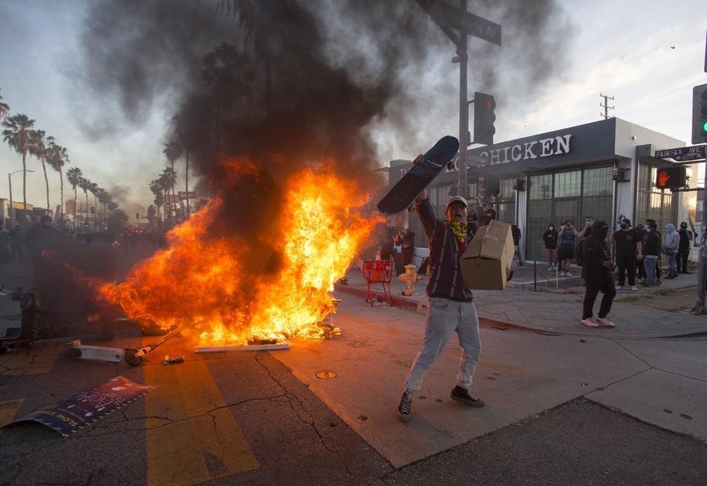 Manifestante grita em frente a um incêndio durante protesto em Los Angeles, na Califórnia, no sábado (30), pela morte de George Floyd. — Foto: Ringo H.W. Chiu/AP