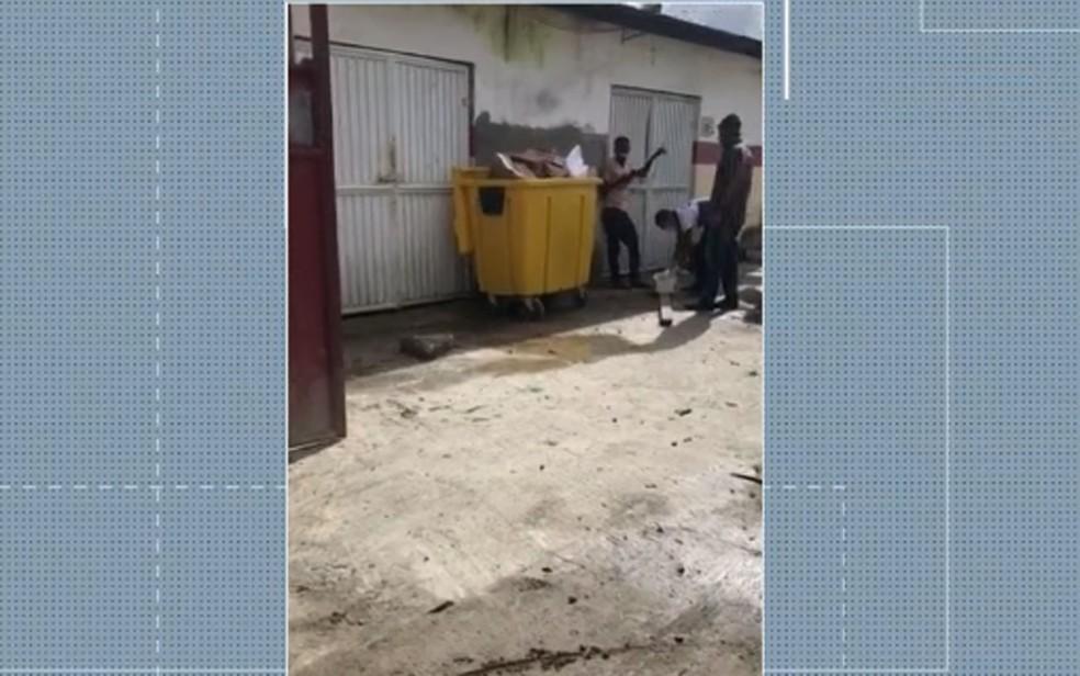 Criança morre em hospital de Candeias e família 'arruma' corpo em caixão do lado de fora de unidade, ao lado de caixa de lixo — Foto: Reprodução/TV Bahia