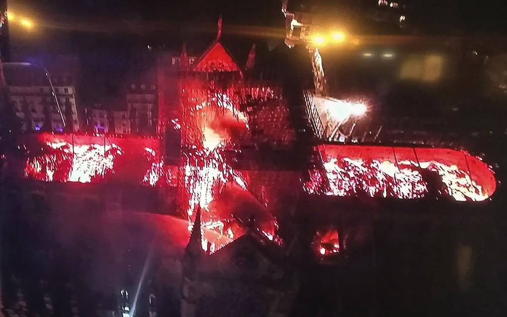 Imagem retirada de tela de TV mostra visão aérea da Catedral de Notre-Dame, em Paris, durante incêndio na segunda-feira (15) — Foto: Stringer/AFP