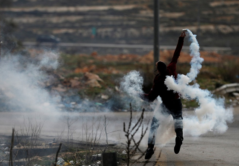 Manifestante palestino joga gás lacrimogêneo de volta contra a polícia israelense durante protesto perto do assentamento perto de Ramallah   (Foto: Mohamad Torokman/ Reuters)