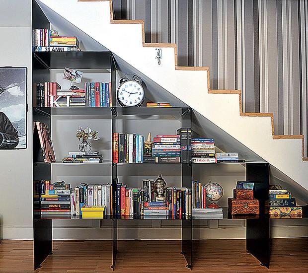 Para aproveitar o espaço sob a escada, os arquitetos Marcos Marcelino e Roberta Martins fizeram uma estante metálica para guardar livros e expor objetos de decoração (Foto: Edu Castello)