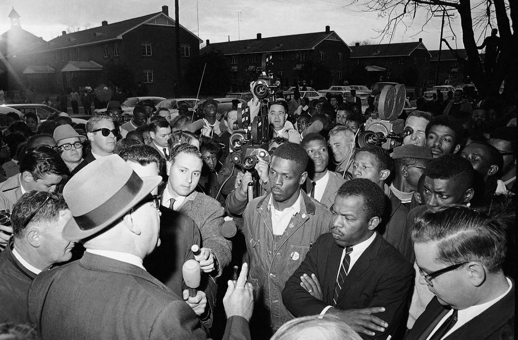 Foto de 23 de fevereiro de 1965 mostra diretor de segurança pública Wilson Baker falando sobre os perigos de manifestações noturnas no início de uma marcha em Selma, no Alabama. John Lewis está no primeiro plano do lado direito — Foto: Associated Press