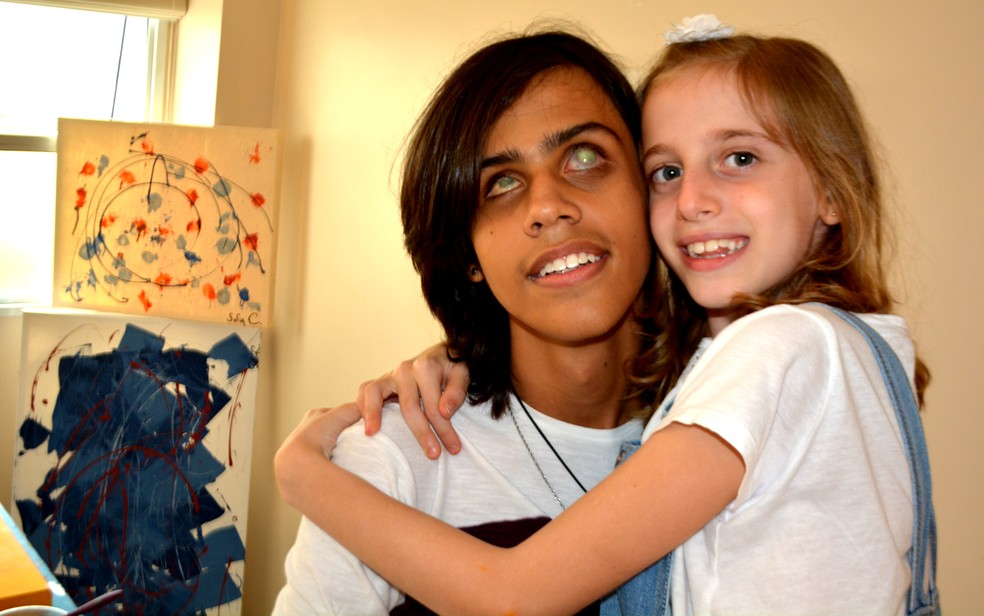 Sofia e Vinícius se consideram irmãos. Artista, ela pinta telas para arrecadar dinheiro para o transplante de córnea dele, em Campinas (Foto: Patrícia Teixeira/G1)