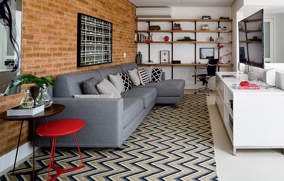 Para otimizar o espaço, a saída dos arquitetos Carla Mattioli e Maurício Pinheiro foi unir sala de TV e escritório no andar de cima da casa de três pavimentos. Predomina a sobriedade, mas os detalhes levam cores marcantes