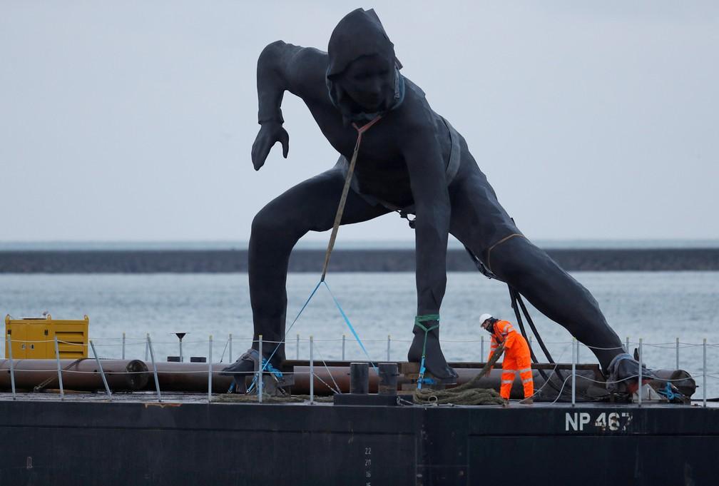 'Mensageiro', a maior escultura em bronze do Reino Unido, é vista durante chegada em Plymouth Sound, na Inglaterra, antes de ser levada para o Theatre Royal — Foto: Peter Nicholls/Reuters