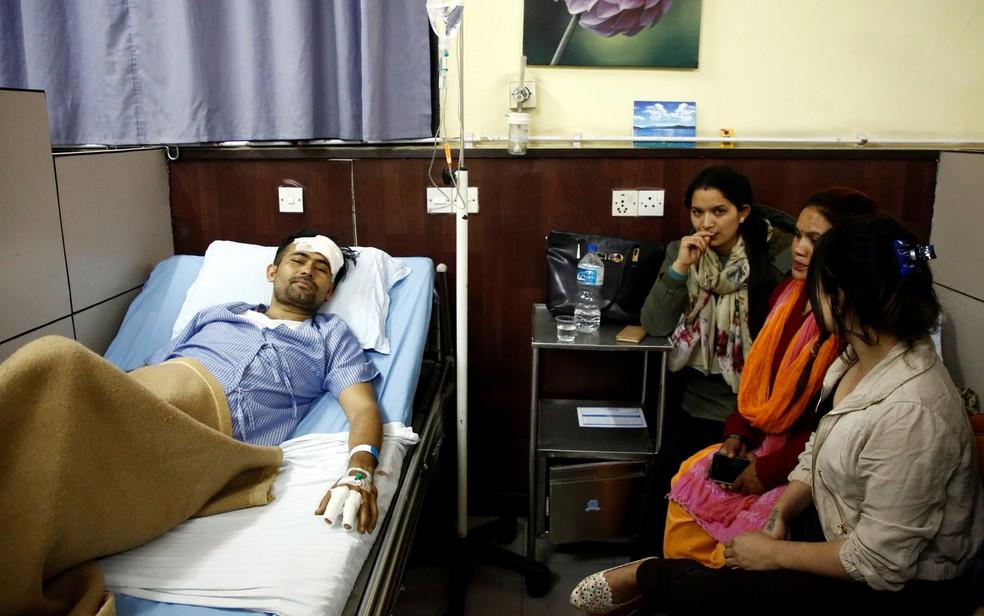 Basanta Bohara, de 27 anos, sovrevivente do acidente de avião no aeroporto de Katmandu, no Nepal, é visto em hospital ao lado de familiares na segunda-feira (12) (Foto: Reuters/Navesh Chitrakar)