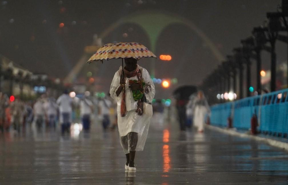 Mulher tenta se proteger da chuva na Sapucaí — Foto: Marcos Serra Lima/G1