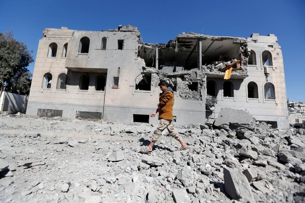 Militante houthi caminha em frente a campo de prisioneiros bombardeado em Sanaa, no Iêmen (Foto: Khaled Abdullah/Reuters)