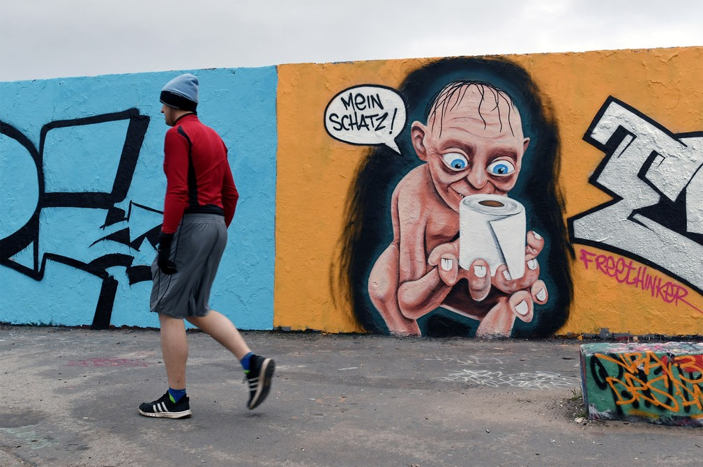 Homem passa por um grafite que mostra o personagem Gollum, da série de livros e filmes 'Senhor dos Anéis', segurando um rolo de papel higiênico e chamando-o de 'Meu precioso' (em alemão). A arte foi feita em uma rua de Berlim, na Alemanha — Foto: Annegret Hilse/Reuters