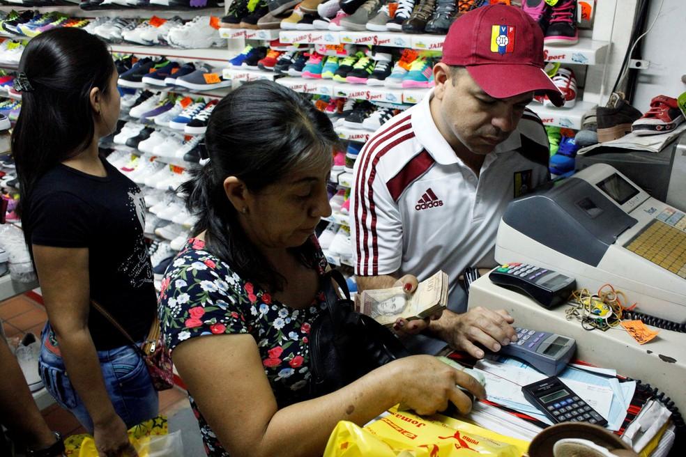 Pessoas fazem compras usando notas de cem bolívares em um mercado de San Cristóbal, na Venezuela (Foto: Reuters/Carlos Eduardo Ramirez)