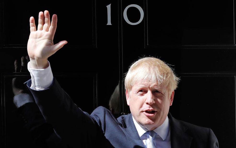 O primeiro-ministro britânico, Boris Johnson, acena em frente ao número 10 de Downing Street, em Londres, na quarta-feira (24) — Foto: AP Photo/Frank Augstein