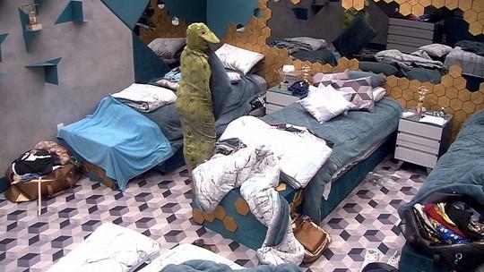 Carolina pega as roupas de cama com a boca
